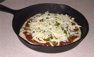 pizza in an iron skillet, ready to cook