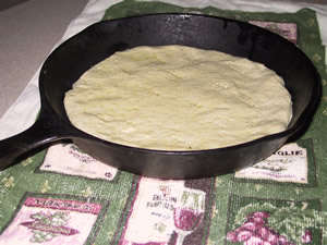 pizza dough in iron skillet, ready for toppings